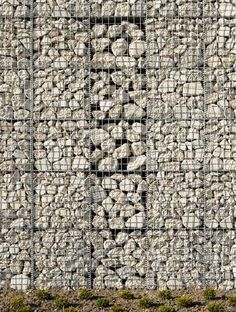 """A gabion (from Italian gabbione meaning """"big cage""""; from Italian gabbia and Latin cavea meaning """"cage"""") is a cage, cylinder, or box filled with rocks, concrete, or sometimes sand and soil for use in civil engineering, road building, and military applications. For erosion control, caged riprap is used. For dams or in foundation construction, cylindrical metal structures are used."""