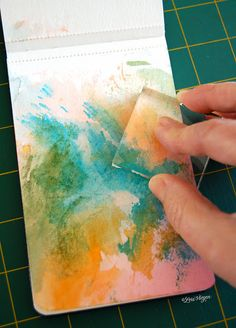 Water soluble Tombow Brush Pen color is brushed on an acrylic block. It's misted with a mini-mister and rubbed across the paper, in as many colors and layers as desired. Diluted white gesso is applied and allowed to dry in areas where you want to write in your journal. Visit link for more details.