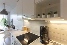 Yksiön toimiva keittiö tilanjakajana eteisen ja ruokatilan välillä.