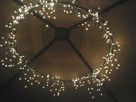 1 hula hoop (spray painted) + 2 strings of icicle lights and a bit o' duct tape = magnificent  chandelier. (outdoor dining area!)