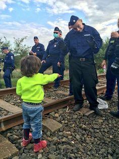 Y el niño refugiado le ofrece una galleta al policía húngaro. Foto @carloangerer