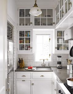 """Note the designer's detailed use of rounded subway tiles on all edges. """"We like the idea of soft and continuous flow of the walls, no sharp corners."""" The use of white bronze for the hardware, from Sun Valley Bronze, also lends the kitchen a visual richness. All panes in the cabinets are restoration glass, which is uneven.   - HouseBeautiful.com"""