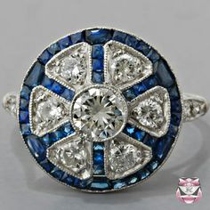 """""""center stone is delicately encompassed by 0.85ct of custom-cut 'lively medium-blue' colored French-cut sapphires graded 'good' clarity"""""""