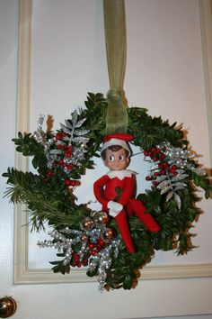 small grapevine wreath I bought at the dollar store and put cut Boxwood stuck in it with some glass and silver and red berries. And guess who our own Elf on the Shelf Aaron.