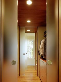 Walk-through closet to bathroom with frosted pocket doors.