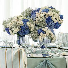 Centro de mesa con hortensias azules y rosas color crema.