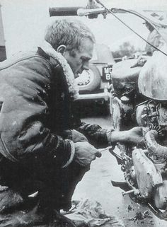 Steve McQueen tinkering with his motorcycle on the set of The War Lover.