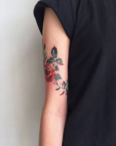 Red peony tattoo on the right upper arm.