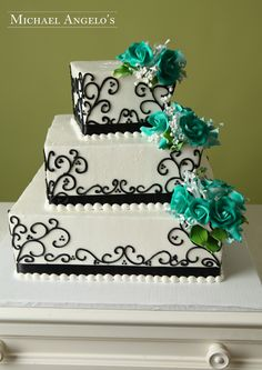 Black & Teal #31Floral This three-tier buttercream square cake is wrapped in a black satin ribbon and decorated with a unique swirl that goes higher on the corners. It then has cascading teal roses coming down the one side.