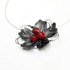 Máky z cínu cínovaný šperk s korálem Jevyroben tiffany technikou s použitím bezolovnatého cínu;šperk je pájen, leštěn, patinován, ošetřen antioxidantem azavěšen naobruči. Náhrdelník je zařazen do soutěže ŠPERK PROs názvem Šperk pro květinové rukávy. Hlasovací blogZDE.