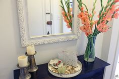 Mirror, flowers ans a bowl for keys. Entry way- check