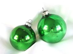 The two beautiful, plain green vintage Christmas ornaments are two different size ornaments.