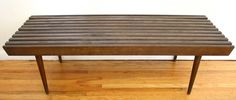 Mid Century Modern Slatted Wood Coffee Table Bench - This is a mid century modern slatted bench made of solid wood.  It has a rich espresso color, a beautiful angled design and the signature mcm tapered legs.  Great as a coffee table or a bench.  Dimensions: 48″ W x 18″D x 14.5″  AVAILABLE