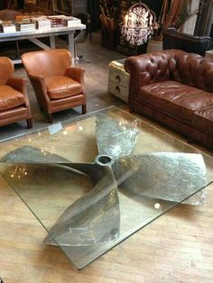 Diy industrial furnitute design using a huge propeller as a coffe table base with a glass top .