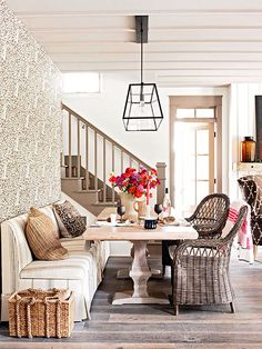 Love the weathered Trestle Table, bench upholstered in ticking fabric and wicker chairs. Love the light fixture too