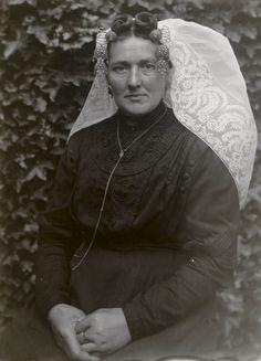 Mevrouw J. Markusse-Leendertse uit Kamperland in Noord-Bevelandse streekdracht. 1916 Mevrouw Markusse is gekleed in uitgaansdracht. Ze draagt delange sluiermuts met 'catrieljebellen' aan de 'krullen' van het oorijzer. Tussen de krullen twee 'torenspelden', waarmee de muts aan het oorijzer is gespeld. Het haar is in 'draaitjes' gelegd. #NoordBeveland #Zeeland