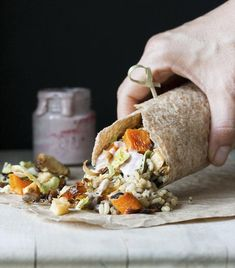 Hand holding burrito filed with roasted fall vegetables, rice and vegan mayo
