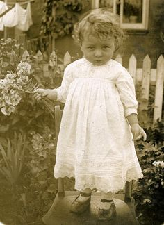 Found image. Another picture of a child balanced precariously on a chair with the washing in the background..
