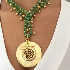 Collar largo de cristal de roca adornado con medallón y libélula pequeña todo bañadoen oro mate y adornada con bolitas pequeñas también bañadas en oro mate. La
