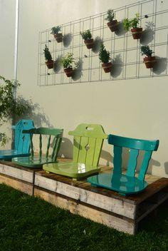 Een bankje van pallets met oude stoelen van de kringloop die we hebben geverfd in verschillende groentinten.