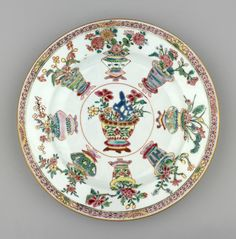 A Chinese famille rose porcelain plate painted at the centre w vase of flowers & blue rock enclosed by orange circle, 8 other vases of flowers on stands painted about outside of reserve; pink diaper band about rim w yellow & gold blossoms.