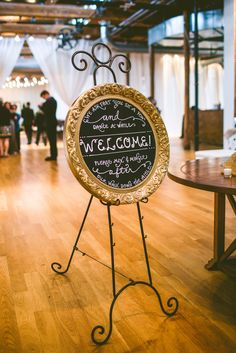 Modern and Industrial gold circular welcome chalkboard | CAROLYN SCOTT PHOTOGRAPHY |  THE COTTON ROOM | CALLIGRAPHY BY CARRIE | https://www.theknot.com/marketplace/carolyn-scott-photography-durham-nc-484266 | https://www.theknot.com/real-weddings/a-modern-industrial-wedding-at-the-cotton-room-in-durham-north-carolina-album