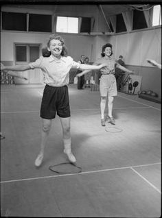 """FACTORY WELFARE WORK: WELFARE AT PILKINGTON'S GLASS FACTORY, ST HELENS, LANCASHIRE, ENGLAND, UK, 1944   D 20079  Women do stride jumps in the gymnasium at the factory rehabilitation centre, (probably at Pilkington's glass works at St Helens), as part of their recovery after an injury. According to the original caption """"the aim of [the centre] is to..."""