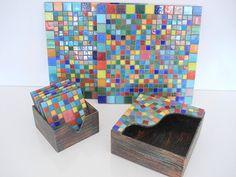 Base MDF, trabalho em mosaico com pastilhas de vidro. <br>Conjunto: 1 Caixa de Descansos para Copo com 6 unidades e 1 Caixa Porta Guardanapos, 2 Descansos para prato/panela.