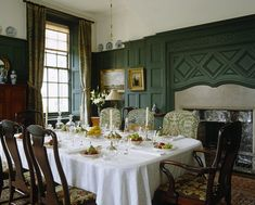 The Dining Room at Standen, West Sussex with the table set for dessert. The green painted panelling follows the original scheme of the room, and the fireplace is by Webb.