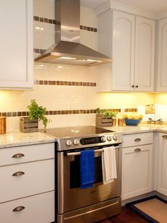 A white and brown striped tile backsplash extends to the ceiling behind the stainless steel range hood. Stainless appliances stand out against the white tile wall and white cabinetry.