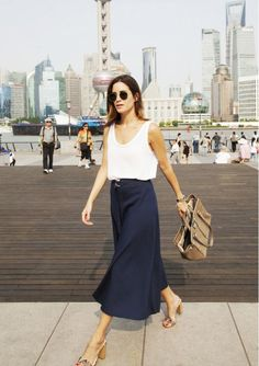 On Gala Gonzalez of Amlul: Zara tank and Midi Skirt ($100) in Navy Blue; Jimmy Choo bag; Guess shoes; Omega watch; RayBan sunglasses