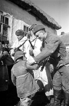 Soviet soldiers of 248th Separate Infantry Brigade (left to right) Sgt. P.N. Tantovoy, Pvt. N.F. Prokudin and Pvt. K.I. Sitkarev greet Russian civilians of a kolkhoz (collective farm) west of Kursk.