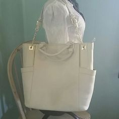 Large White Olivia + Joy Bag Color is just a bit off white. Very large. Room for everything! Perfect summer bag. Kind of like a square bucket bag.  Carry like a satchel or use shoulder straps. Very cute. Only worn twice. Like new. Constructed from PVC vegan leatger. Gold hardware. Gold chain on lower part of straps. High quality and sturdy. 2 deep outside side pockets. Zippered pocket outside and inside. 2 notch pockets inside. Olivia + Joy Bags