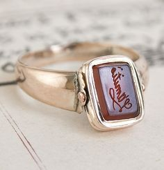 "This swivel-face ring was crafted just under two hundred years ago to mark the death of a man named John Willington. On one side, a carnelian intaglio seal is engraved with the word ""L'Amitie"" (meaning ""friendship"" in French) and is set in 14k rose gold. Spin it around to reveal a slab of glossy black onyx, which was probably added as a replacement - or placeholder - for a plait of the deceased's hair installed under glass."