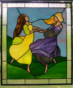 I love this stained glass piece...it is full of joy and happiness as two women dance together in a spring meadow. It suggests to me a long friendship, good news and the warmth of sunshine after a long winter. The panel is 16 1/4 inches tall and 14 inches wide. Clear textured glass with corner bevels frames the scene. I used 10 different kinds of glass from several manufacturers for the main focal point; most of it is opalescent glass with a few cathedral glass highlights on the womens yellow…