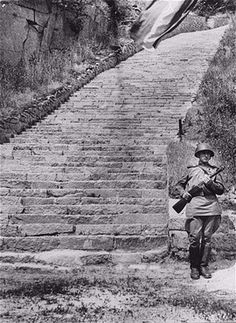 """A Soviet honor guard stands before the """"Todesstiege"""" (The Stairs of Death) in the Mauthausen concentration camp. Nazis forced prisoners to repeatedly carry heavy granite blocks up these stairs until they died or were murdered if they failed.-lib5.jpg 270×370 pixels"""