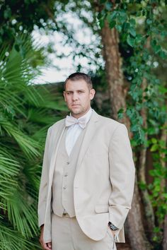 Groom stands by palm trees, Creek Club at I'on, Charleston, South Carolina. Kate Timbers Photography. http://katetimbers.com #katetimbersphotography // Charleston Wedding Photography // Posing Inspiration