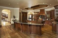 kitchen - love the dark wood, the chandeleir over the island, the back splash.... and look at that iron staircase rail!