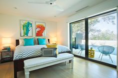 Host Jennie Garth of The Jennie Garth Project designs a modern, colorful guest bedroom. Abstract art and pillows add pops of color to the neutral space, while sliding glass doors open to a contemporary patio.