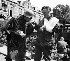 A wounded British paratrooper shares his meal with a German soldier at Arnhem September 1944.