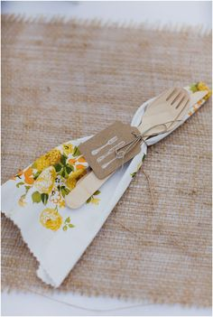 Spur of the moment decision to use biodegradable, organic bamboo flatware. Cheap, cute, and fits directly in with the sustainable theme! Adorned with vintage print napkins, twine, an adorable tag and a sprig of lavender