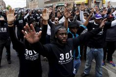 Freddie Gray protestors stand with arms open against police brutality. Photo from Jim Bourg/Reuters.