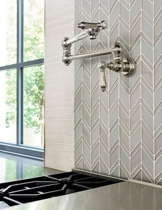Chic kitchen features a swing-arm pot filler lining a gray and blue glass chevron tiled backsplash placed over a gas cooktop.