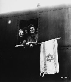 Jewish children holding the Israeli flag while hanging out of a train window after having been released from Buchenwald Concentration Camp, on their way to Palestine at the end of World War II. Photograph by James E. Myers. Germany, June 1945.