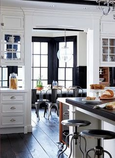 Upper cabinets with glass on both sides let the light in and connect the kitchen to the breakfast nook beyond.
