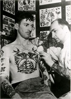 The photograph, circa 1943, shows L. M. Brown, a sailor, getting tattooed by Owen Jenson