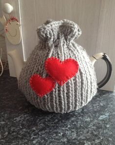 Knitted tea cosy in chunky grey wool with little red heart detail via Etsy