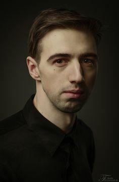 formal studio portrait. three-point lighting. low-key.