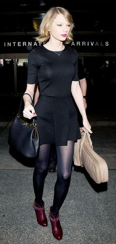 Taylor Swift wears a black t-shirt and circle skirt with black tights and red heels.