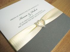 Albany Order of Service in white and grey and finished with pale yellow ribbon and a crystal heart.